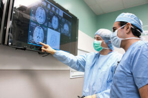 Dr. Leuthardt looks at a screen of a brain image